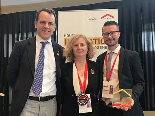 Le président et premier dirigeant de la SCHL, Evan Siddal, accompagné de représentants des équipes gagnantes de la Médaille du président et du Prix pour l'excellence en recherche sur le logement.