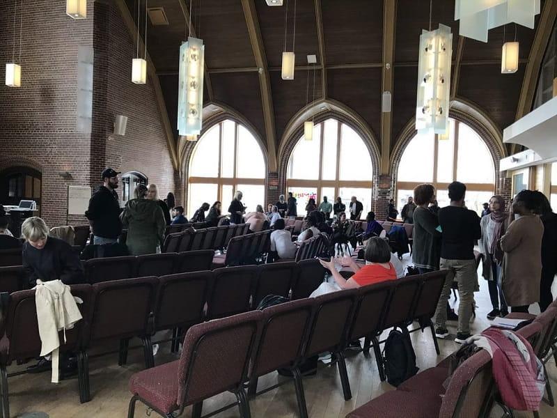 Groupes de personnes discutant du logement dans une grande salle pendant les journées de co-conception.